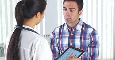 Un profesional de la salud que habla con un paciente en su oficina