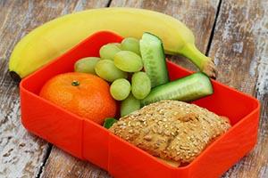 Alimentos ricos en fibra , incluyendo un plátano , una naranja , uva , pepino , y un sándwich con pan integral
